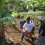 Jason Menaling, a Pulangiyen youth leader, shows students how to plant bananas