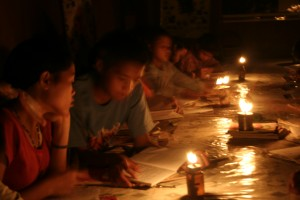 Kids studying by oil lamps at night